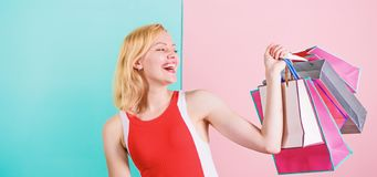 Buy everything you want. Girl satisfied with shopping. Girl enjoy shopping or just got birthday gifts. Woman red dress. Hold bunch shopping bags blue pink royalty free stock images