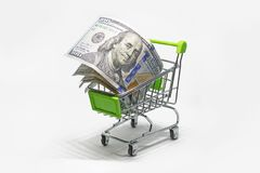 Shopping basket with dollar bank notes, bills isolated on white background. Buy foreign currency. Purchase of banknotes 100 dollar. Shopping basket with dollar Stock Photos
