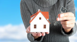 Buy a house. Girl holding a house with the key Stock Photos