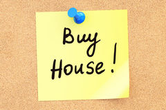 Buy House! Text on a sticky note pinned to a corkboard. 3D rende Stock Photos