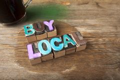 Buy Local - Wooden typeset word concept. Buy Local  in multicolor wooden letterpress letter printing blocks with retro camera lens Royalty Free Stock Photo