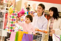 Buy me that. Image of cute toddler showing something to her parents in shop while they looking at it with smiles Royalty Free Stock Photo