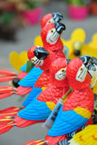 Buy me! - decorative parrot standing out in a row. A row of decorative parrot toys with one standing out and looking at the viewer; sharp and narrow depth of stock photos