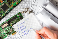 Buy a new computer instead of a broken computer. A hand hold a pen and write, schemes on the table royalty free stock image