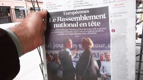 Buy Newspaper featuring Marine Le Pen and Jordan Bardella. Strasbourg, France - May 27, 2019: Man holding buying La Croix newspaper front page on street press stock video