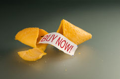 Buy now fortune cookie. Broken open fortune cookie with a fortune message of BUY NOW stock image