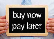 Buy now and pay later - shopping and finance. Buy now and pay later - manager holding chalkboard with text in his hands royalty free stock photos