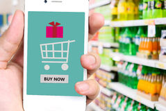 Buy now on smart phone screen in hand with blurred supermarket b Stock Image
