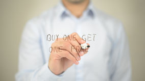 Buy One Get One Free , man writing on transparent screen stock photo