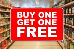 Buy one get one free red label on an abstract Supermarket background royalty free stock photo