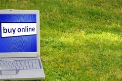 Buy online. Or ecommerce concept with laptop in green grass Royalty Free Stock Photos