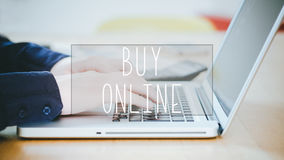 Buy Online, text over young man typing on laptop at desk. Buy Online, text over young business man typing on laptop at desk in office environment stock photography