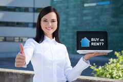 Buy or rent - beautiful business woman showing laptop with real. Estate application on screen Royalty Free Stock Image
