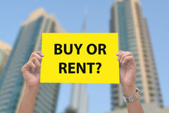 Buy or Rent Property Sign in Hand. A men holding buy or rent property sign with apartments in the background royalty free stock image