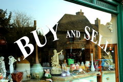 Buy & Sale. A sign in a shop window indicating that they both buy and sell items Stock Image