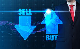 Buy and sell arrow. Businessman drawing buy and sell arrow on virtual screen royalty free stock photos