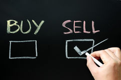 Buy and sell check boxes. On a blackboard, with sell cheched. Finance, economy, stock or real estate concept - time to buy or sell stock image