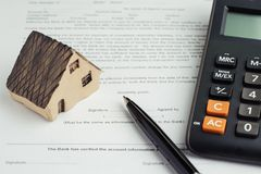 Buy and sell house, mortgage calculation and contract signing co. Ncept, miniature house on printed paper document and pen to sign agreement contract with royalty free stock photography