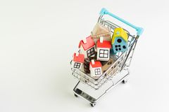 Buy and sell house, property demand and supply on real estate purchasing concept, shopping cart or trolley with full of small cute royalty free stock photography