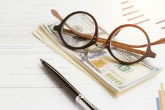 Buy and sell or leasing contract against bank, eyeglasses on pile of US dollar banknotes, printed paper form with pen to sign doc. Ument with graph and price royalty free stock photography