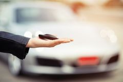 Car key, businessman handing over gives the car key to the other man on car background. Buy-sell a new car with a request for a low-interest loan and a car stock image