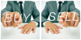 Buy/sell. Pictures of a businessman sitting in a desk pointing the words buy and sell written in the foreground stock images