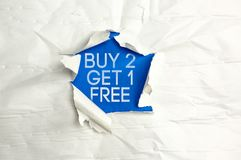 Buy two get 1 free. Torn paper writing Buy two get 1 free Stock Photo