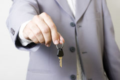Buy your house. Hand holding a home key Stock Image