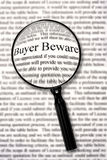 Buyer Beware. Magnifying glass over contract document, highlighting words buyer beware royalty free stock image