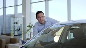 Buyer car shows thumbs up, Auto business, car sale, technology and people concept - happy male client in auto show or stock video footage