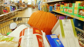 The buyer carries a cart with purchases through the store. The trolley is also a pumpkin. Preparing for Halloween stock footage