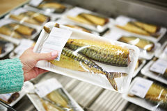 Buyer chooses smoked fish mackerel Royalty Free Stock Photos