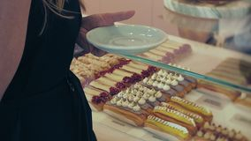 She buyer chooses yummy. Young attractive girl, woman buys in the coffee shop or pastries, cakes, cake, macaroon. A stock video footage