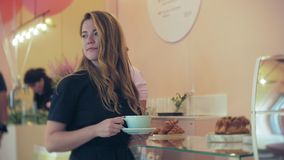 She buyer chooses yummy. Young attractive girl, woman buys in the coffee shop or pastries, cakes, cake, macaroon. A stock footage