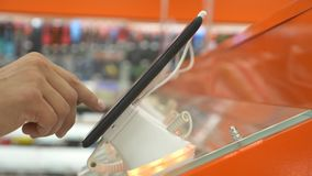 The buyer in the electronics store chooses a new gadget. 4k, close-up, blur background. Looking for a new peace of stock footage
