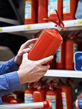 Buyer with fire extinguisher in hands at store Royalty Free Stock Image
