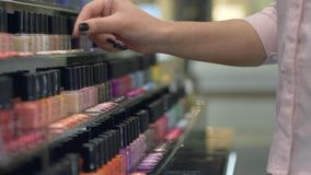 Buyer Girl chooses nail polish for manicure and pedicure from large number of bottles of nail varnish on shop showcase. Hands close-up stock footage