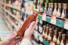 Buyer hands with bottle of sauce in store Stock Photos