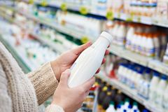 Buyer hands with bottle of milk at grocery Stock Image