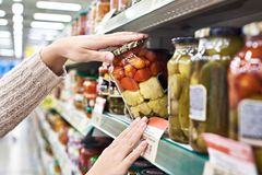 Buyer hands with jar of salted tomatoes and squash in store Stock Image