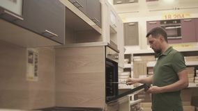 Buyer is inspecting showpiece of oven in kitchen in a furniture store