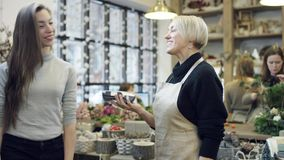 The buyer pays for the purchase through the card to the florist in black sweatshirt. The buyer pays for the purchase with a credit card and florist, at the end stock video footage