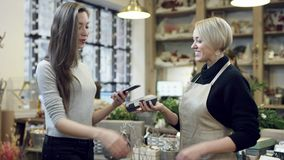 The buyer pays for the purchase through the phone and florist in black sweatshirt gives to her shopping bags. The buyer pays for the purchase with the phone and stock footage