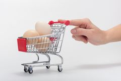 Buyer`s hand pushes a chicken cart with a finger. Buyers hand pushes a chicken cart with a finger royalty free stock photo