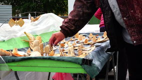 The buyer sees on the table homemade carved statuettes and figurines of wood.  stock footage