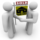 Buyer and Seller Handshake - For Sale Sign. A home buyer and seller shake hands in front of a for sale sign that is marked Sold Stock Photo