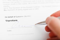 Buyer signing sales contract by silver pen Stock Image