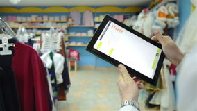 Buyer of the tablet in clothing store stock video footage