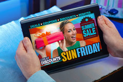 Buyer with tablet at a online shop with an announcement of purchase in sun friday or summer sales. Man searching offers in website store to purchase in Sun stock photos