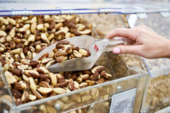 Buyer takes brazil nuts in store Royalty Free Stock Photo